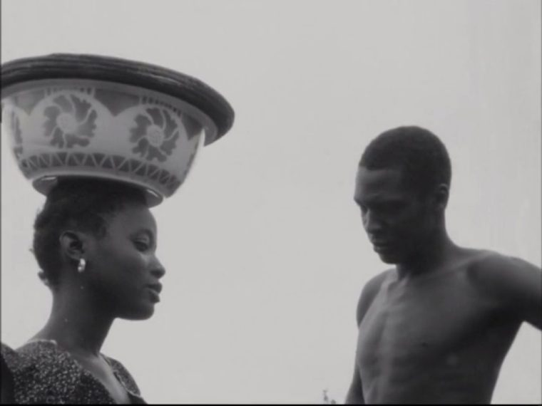 An African woman carries a pot on her head, and confronts a man