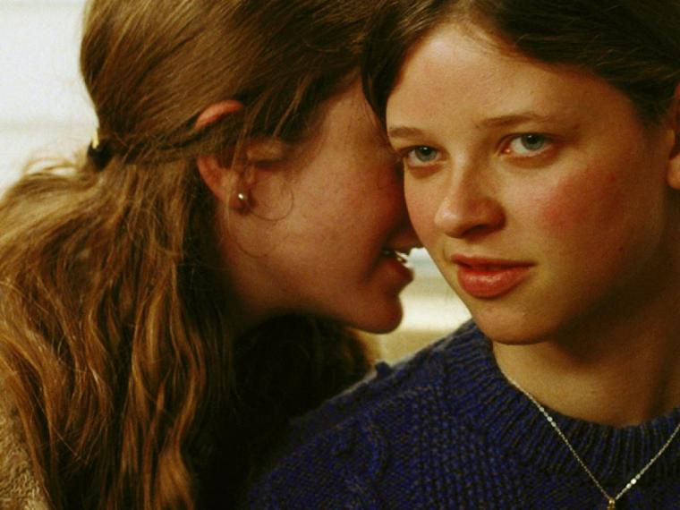 Two young women whisper