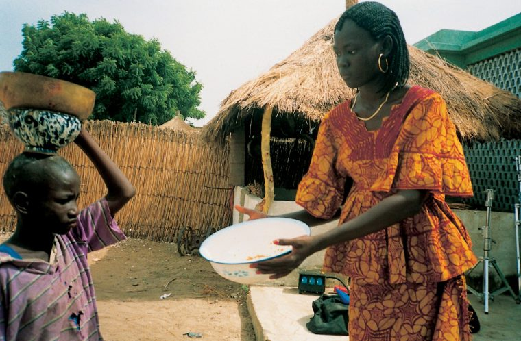 An African girl holds out a bowl