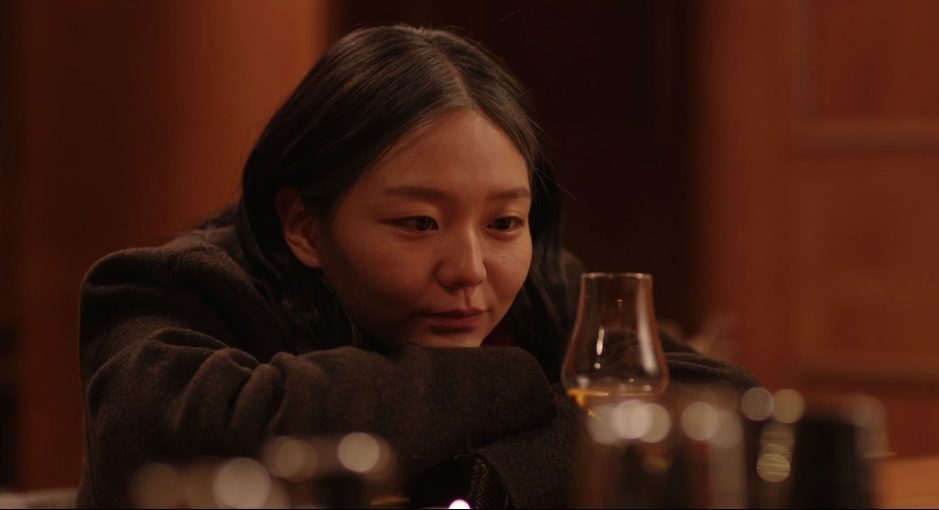 A young Korean woman stares at a glass of whisky
