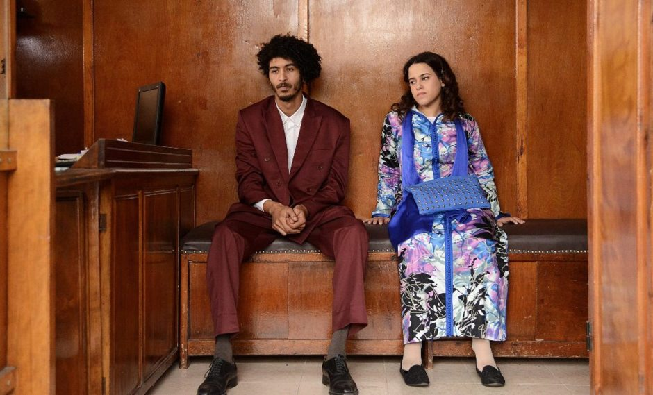 A young Moroccan man and a woman sitting dressed in wedding clothes