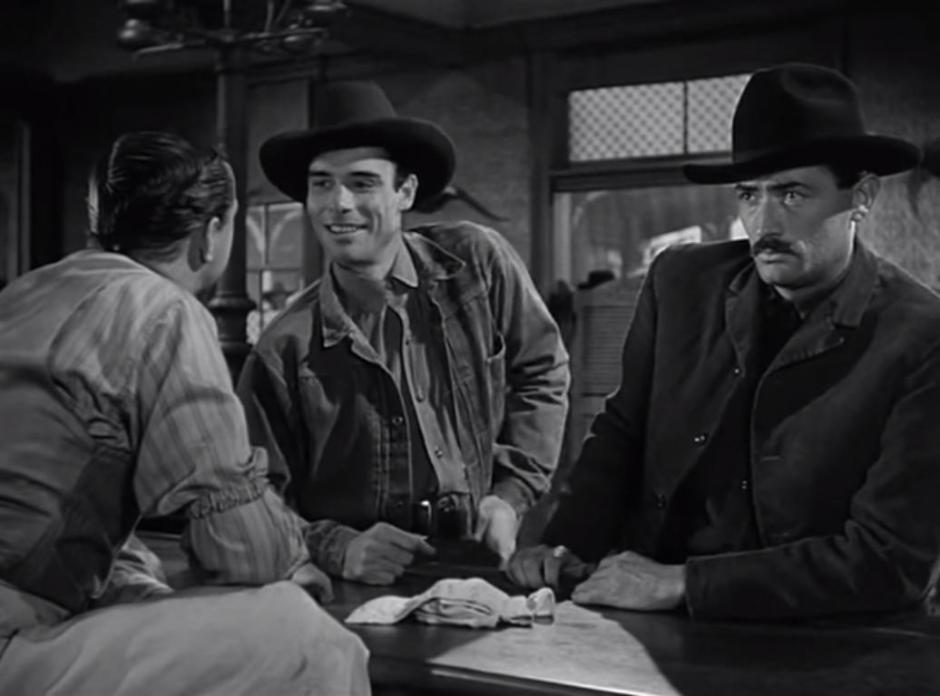 Gregory Peck looks discombobulated, while two other men chat beside him at the bar