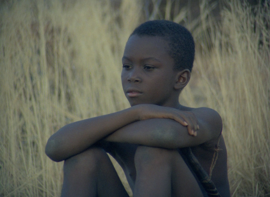 An African boy sits by himself amongst some grass