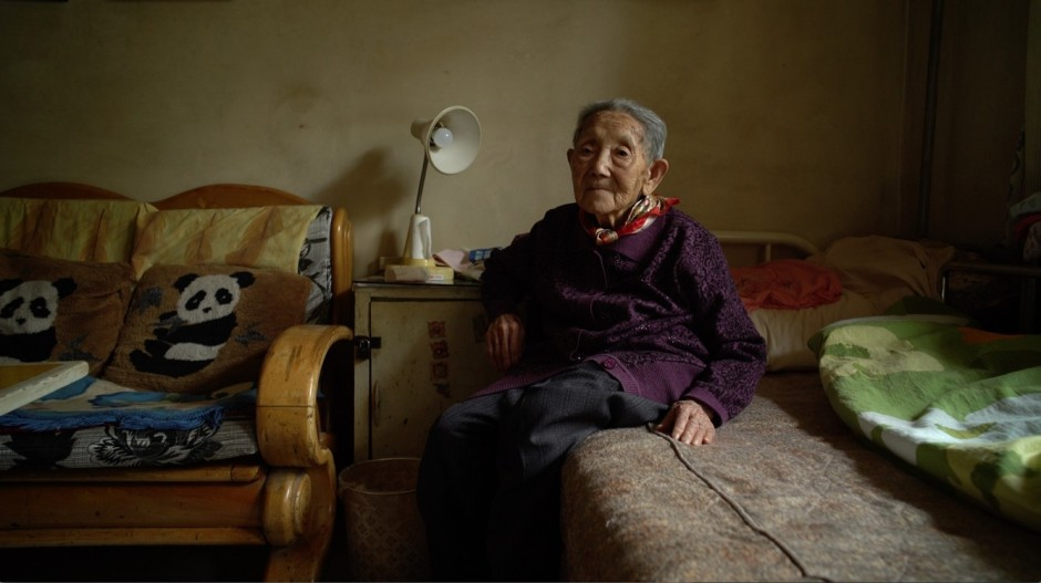 An elderly Chinese woman sits on her bed